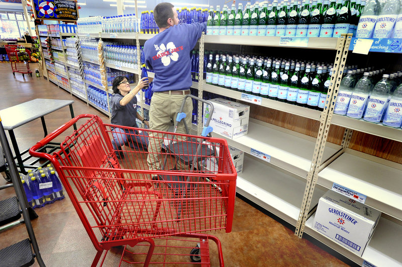 Marianna Reeves, kneeling, and Steve Monks stock bottled water at the Trader Joe's store at 87 Marginal Way in Portland. The store has been drawing fans and onlookers as it readies for Friday's grand opening.