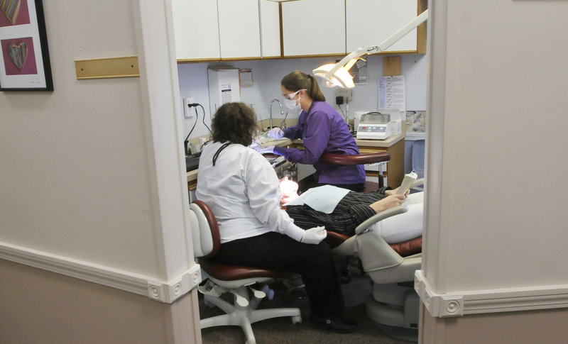 Dr. Denise Theriault and hygienist Stephanie Fortier work on Adriane Williams' teeth during a visit to the Dunstan Dental Center on Friday. Several offices in southern Maine offered free dental care for the day.