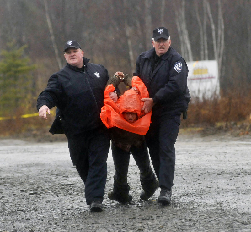 Police officers carry a protester off the site of the Rollins Mountain wind-power project in Lincoln.