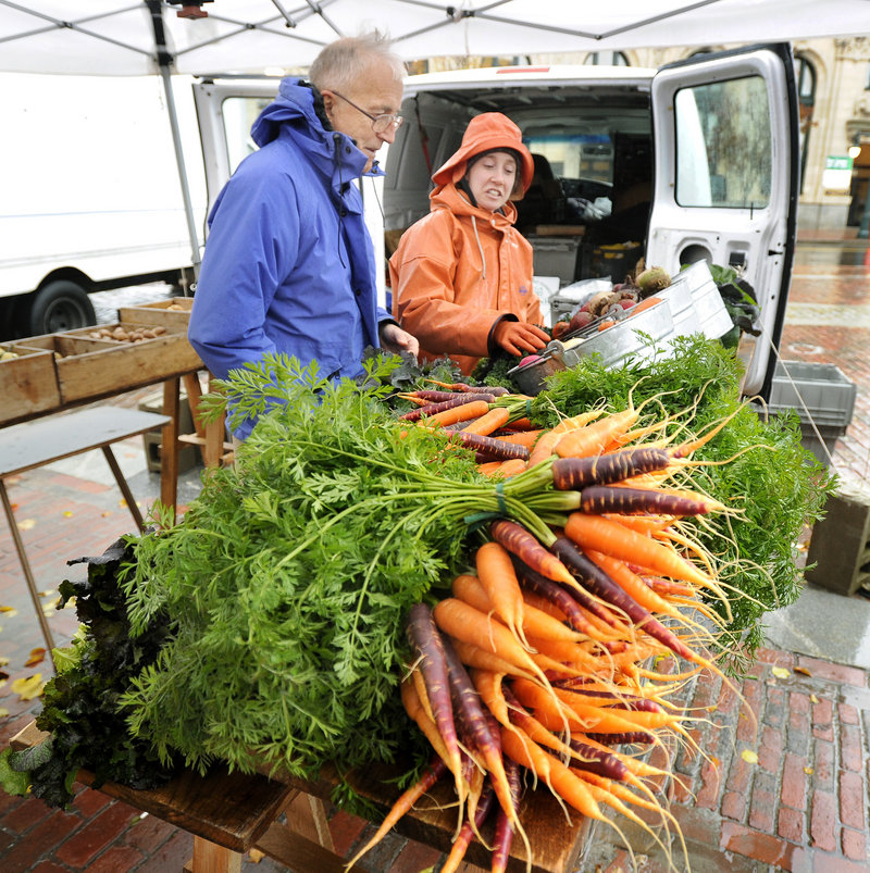 Jeff Brown of Portland buys produce from Mary Ellen Chadd at her Green Spark Farmstand in Monument Square in Portland this month. Growers donated more than 200,000 pounds of their harvests to food pantries, shelters and other charitable groups this year.