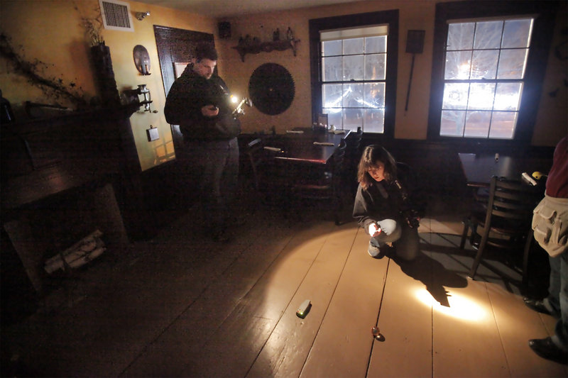 Jennifer Elliott, center, and James Logsdon, left, watch an electromagnetic frequency meter and a ball on the floor as they search for paranormal activity at the Maine Street Grill.