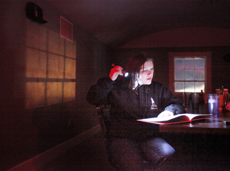 """Mandy James reads """"Twas the Night Before Christmas"""" in an attempt to get a response from a ghost, believed to be a young girl, at the Maine Street Grill. James runs Paranormal Researchers and Investigators of Maine with her husband, Louis Logsdon, and was looking into reports of unusual activity at the Standish restaurant."""