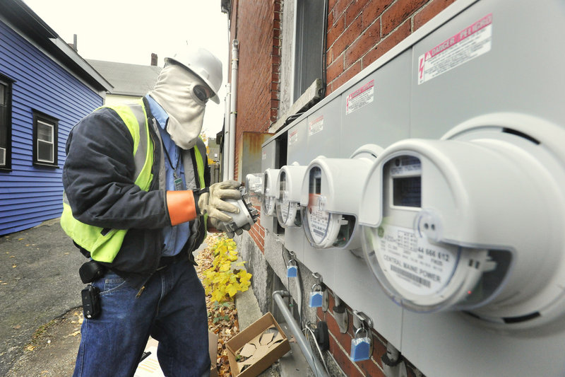 Zach Pomelow, wearing face and hand safety equipment, installs new smart meters at homes on Brackett Street in Portland.