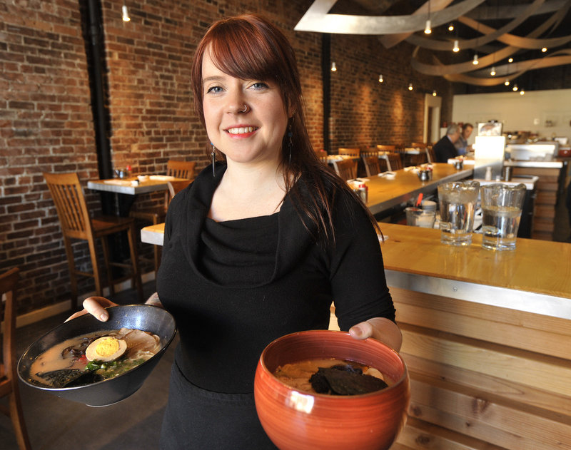 Gemma Hancock, a server at Pai Men Miyake, 188 State St. in Portland, displays a ramen dish and a bowl of spicy miso. The popular new Japanese restaurant is an attractive space, with exposed brick, handsome wood details and artfully arranged metalwork swooping from the ceiling.