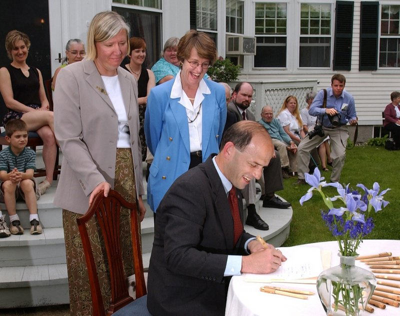 Gov. John Baldacci signs Maine's DirigoHealth initiative into law in 2003, outside the Blaine House in Augusta. He is joined by his wife, Karen, left, and Trish Riley of the Governor's Office of Health Policy and Finance.