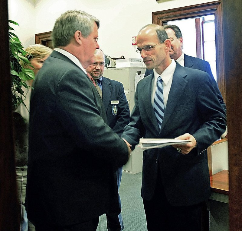 Sen. Dennis Damon, D-Trenton, left, hands Gov. John Baldacci the bill that the Maine Senate passed earlier that day in May 2009 to affirm the right for same-sex couples to marry. Baldacci signed the bill into law that day.