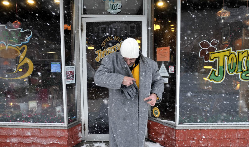 Staff photo by Michael G. Seamans Tony7 Karter budles up as he leaves the warm confines of Jorgensen's Cafe on Main Street in heavy snow Wednesday morning in Waterville. The storm moved further inland then previously forecasted.