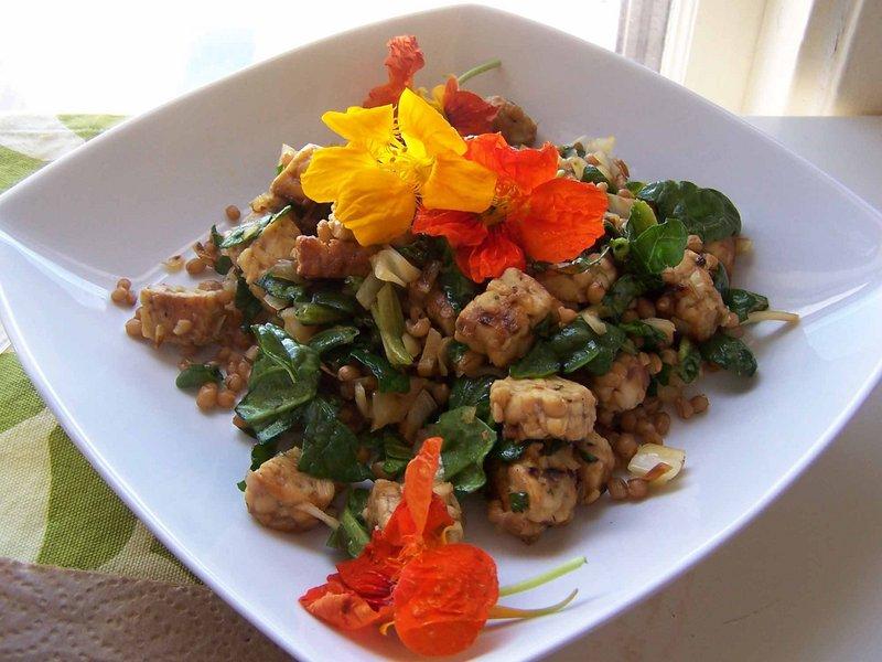 Sweet and spicy tempeh salad with nasturtium garnish.