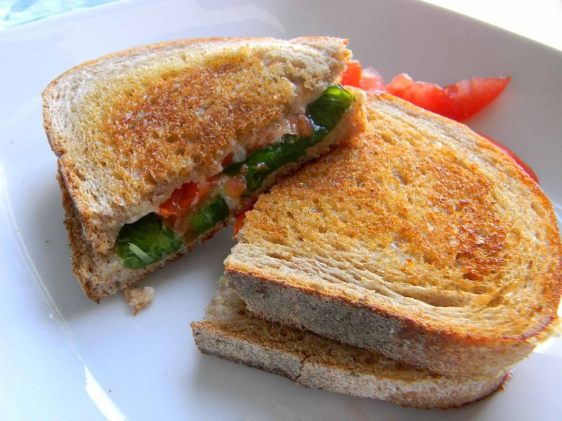 Grilled cheese sandwich with greenhouse-grown tomatoes and basil.