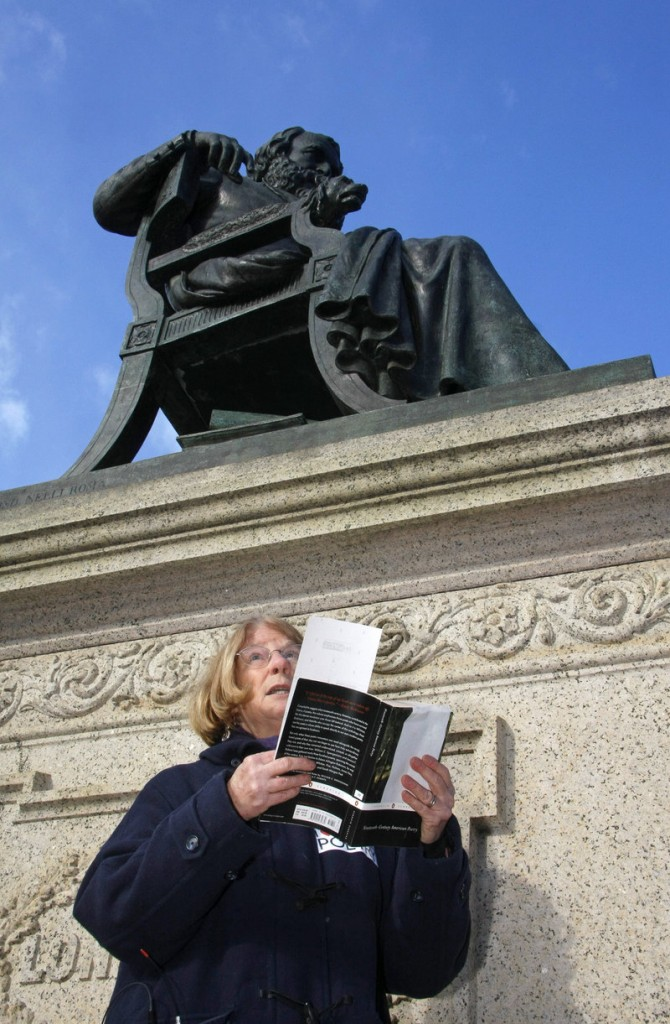"Elizabeth ""Betsy"" Sholl, Maine's poet laureate, reads under the statue of Henry Wadsworth Longfellow on Wednesday in an event organized to celebrate poetry."