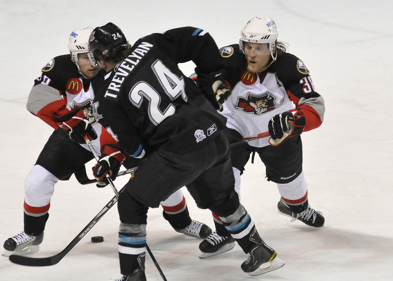 Portland Pirates Brian Roloff, left, and Tim Conboy, right, try to separate Worcester s T.J. Trevelyan from the puck Saturday night at the Cumberland County Civic Center.