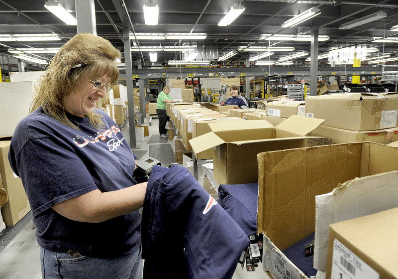 Wendy Levasseur sorts T-shirts at Olympia Sports' distribution center in Westbrook. Olympia ships an average of 4,000 boxes to stores each day.