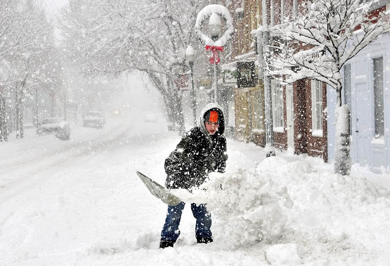 Snow continues to fall as Jacob Chamberland shovels in front of an apartment building this afternoon on Water Street in Gardiner. He said that he and his brother were making some money while school was canceled because of the storm.