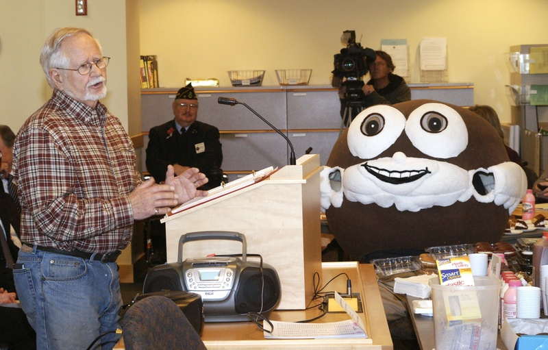 """John Linscott, who wrote lyrics about whoopie pies, testifies last month in Augusta under the watchful eyes of a man dressed as a whoopie pie. On Monday, a legislative panel amended a proposed bill to say that the whoopie pie would be the state's official """"treat."""""""