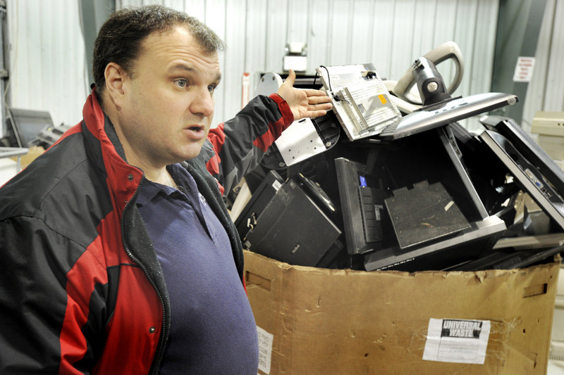 Rick Dumas, CEO of eWaste Recycling Solutions, LLC, in Auburn, points out all of the old TV sets, computer monitors and other electronic devices that await dismantling for recycling.