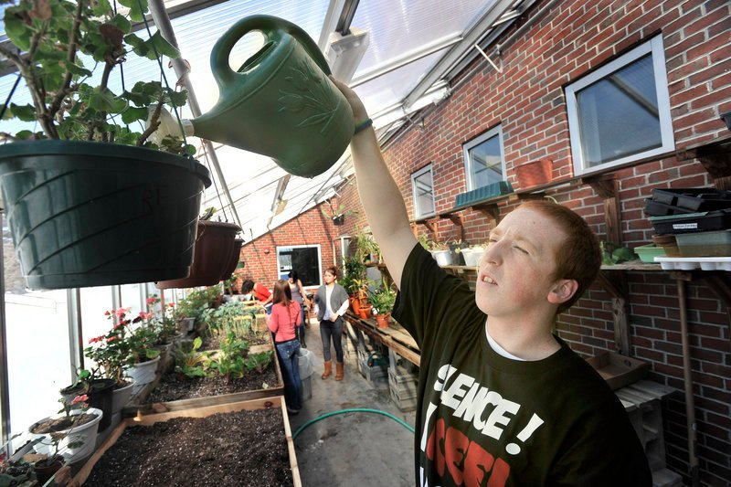 South Portland senior Brandon Gordon waters plants. The greenhouse is part of an effort to bring more experiential learning into the classroom.