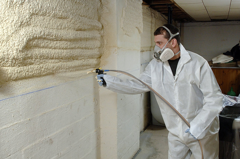 Jim Boilard, a weatherization tech for Weatherize Northeast, sprays foam on basement walls at a Yarmouth home under a program offered by the Maine Housing Authority.