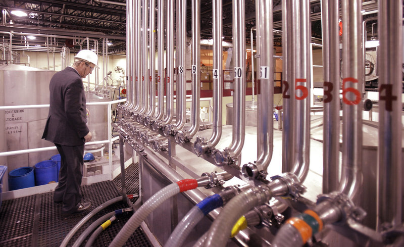 John Suczynski, White Rock's COO and CFO, walks past a row of stainless steel pipes that transport alcohol to the bottling lines at the distillery in Lewiston.