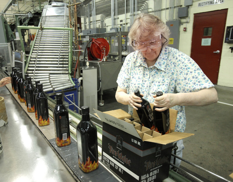 Anita Desrosiers loads bottles of Fire Water, a cinnamon-flavored schnapps, at White Rock Distilleries in Lewiston.