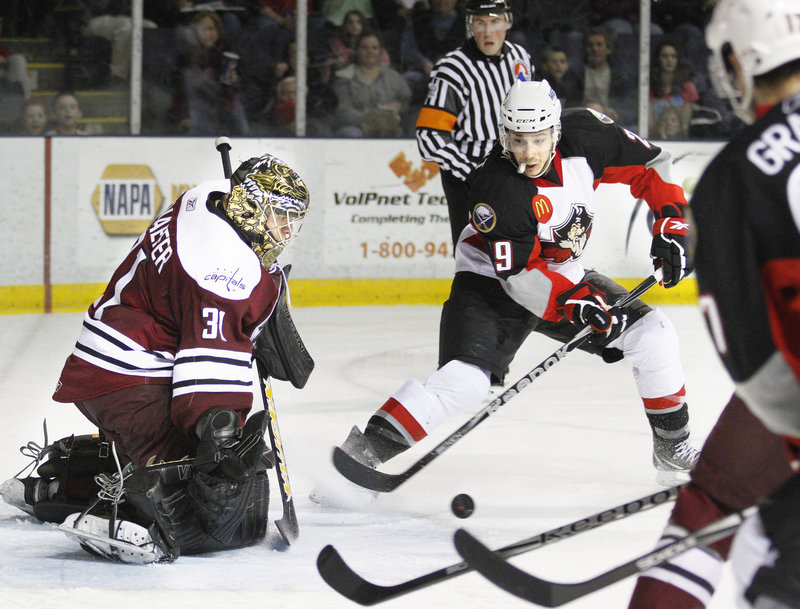 Hershey goalie Nolan Schaefer knocks away a shot by Portland's Maxime Legault in the Pirates shootout victory Tuesday night.