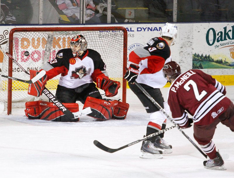 Patrick McNeill of the Hershey Bears sends a shot past defenseman T.J. Brennan and over Portland goalie David Leggio's blocker for the tying goal late in the third period. The Pirates prevailed in a shootout at the Cumberland County Civic Center for their fourth straight victory.