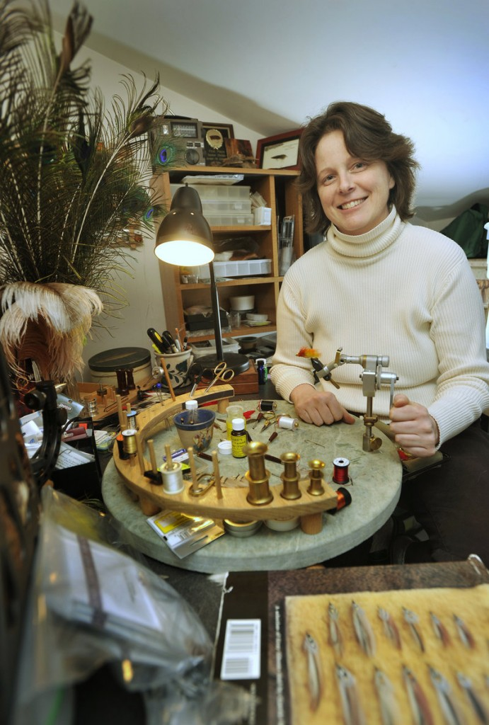 Selene Dumaine ties flies in her tiny workshop at home in Brunswick. Dumaine has built a reputation as a top fly tier, but has found it difficult to earn a living with those skills in hard economic times. She hopes to expand her small business with a fly shop on her property near the Androscoggin River.