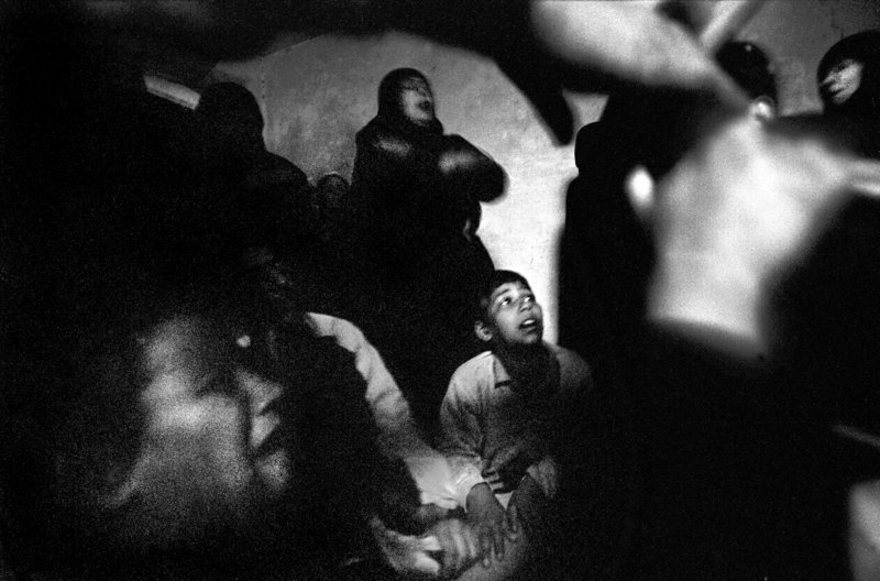Sadr City Shiites pray and wail in the darkness amid bombing and heavy fighting in the Baghdad slum in April 2004. They had gathered in a home for the funeral of a young man killed earlier that day by U.S. soldiers. The April uprising, in which Shiites took up arms against the occupation en masse for the first time, was one of the bloodiest months since the war in Iraq began in 2003.