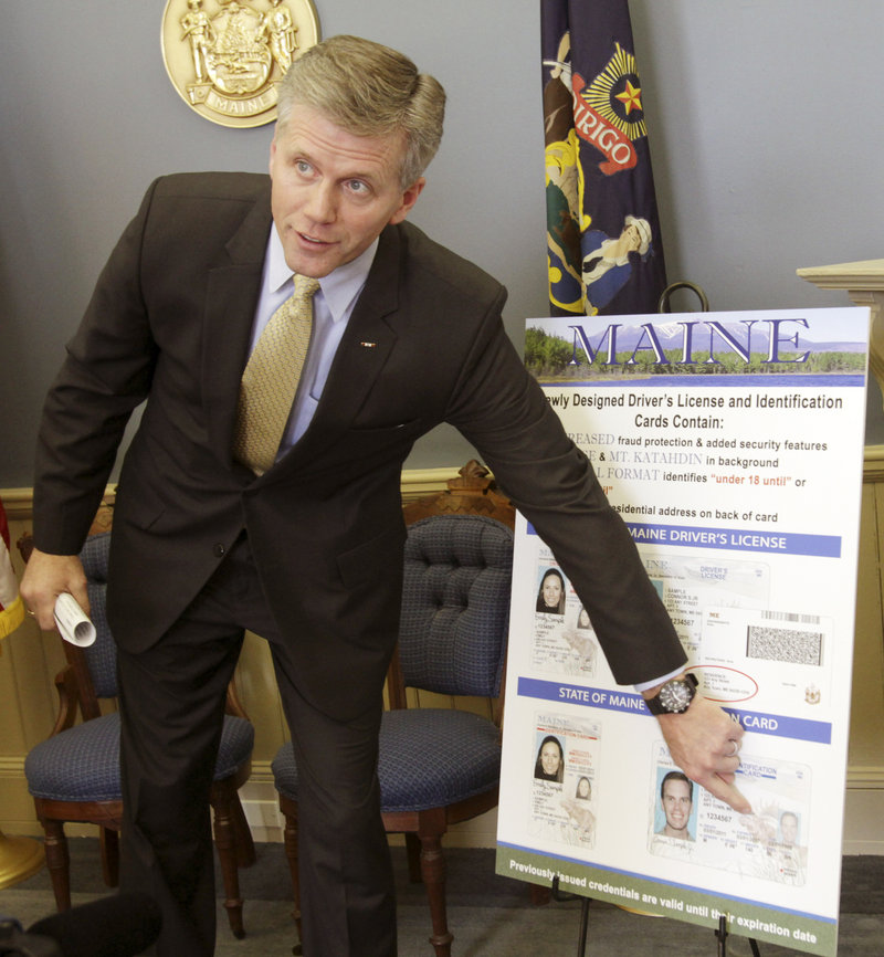 Secretary of State Charlie Summers points to a poster of the new Maine driver's license design, featuring updated security enhancements, at a news conference Tuesday. There also are vertical formats for cardholders below the age of 21.
