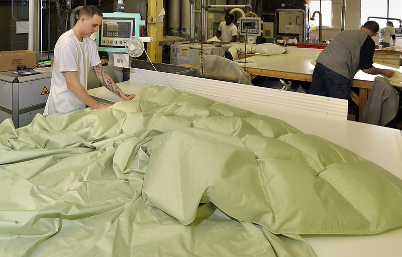 Bobby Hipsher fills a colored baffled comforter with down at the Cuddledown factory in Portland.