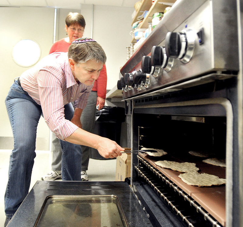 On baking day at Congregation Bet Ha'am in South Portland, Lisa Munderback tends to matzah in the oven as Donna Landau observes.