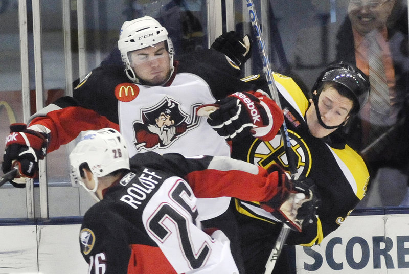 T.J. Brennan of the Pirates checks Adam Estoclet of the Bruins into the boards while Portland's Brian Roloff digs for the puck Tuesday night at the Cumberland County Civic Center. The Pirates won, 3-0.