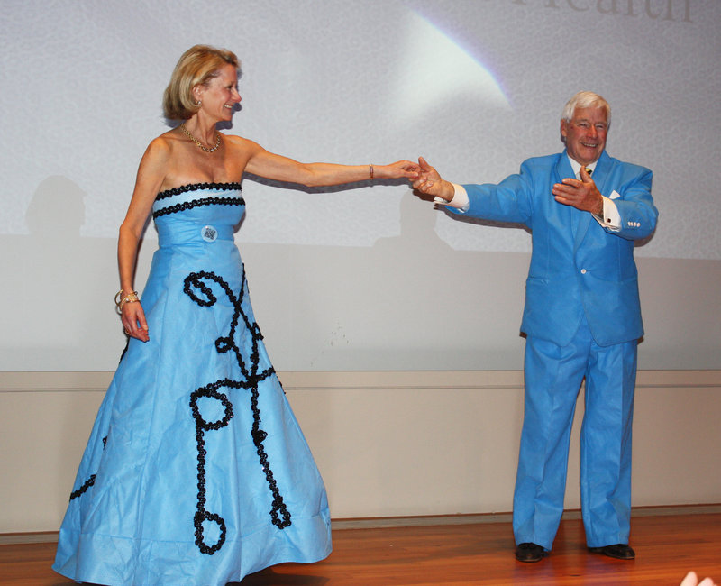 Partners for World Health founder Elizabeth McLellan models a blue wrap ball gown designed by Jung's Quality Creations and is accompanied on the runway by board member Ryan Fendler, who wears a suit created by his family's business, C.M. Almy.