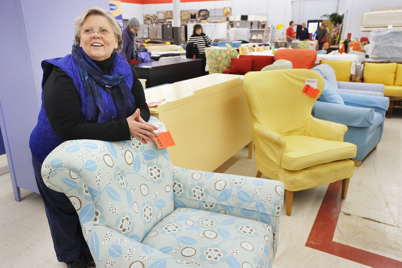 """Ann Bishop of Falmouth stands with three Maine Cottage Furniture chairs that she snagged Tuesday, along with a blue bookcase, at the Marden's store in Scarborough. Bishop said she planned to put her new furniture in a home office and """"get rid of the family antiques."""""""