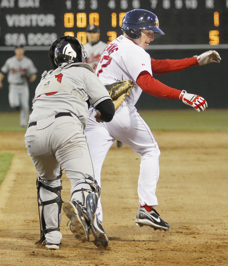 Rock Cats catcher Allan de San Miguel tags out Mitch Dening of the Sea Dogs after a rundown between first and second during a game Thursday night at Hadlock Field. Portland opened a seven-game homestand with a 5-1 win.
