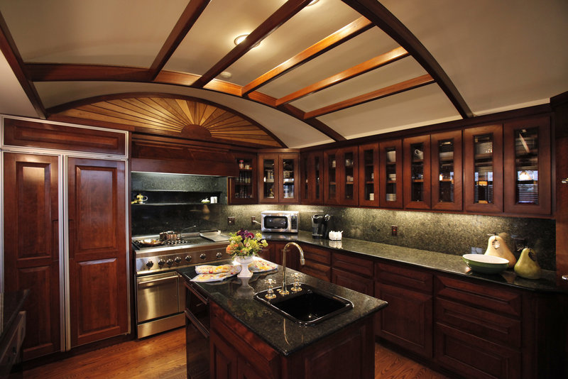 Tanya Preston's kitchen has four ovens, two dishwashers, two warming drawers, an island with a sink, and cherry cabinets. The wood sunburst over the stove is custom-carved.