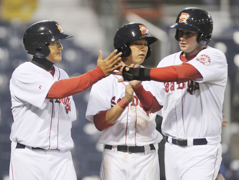 Three Sea Dogs, from left, Che-Hsuan Lin, Jon Hee and Alex Hassan, celebrate after scoring on a double by Tim Federowicz that highlighted a five-run seventh inning Tuesday night during Portland s 8-2 win over Binghamton.