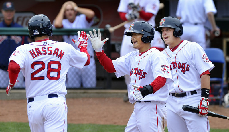 Alex Hassan is welcomed by Che-Hsuan Lin, center, and Ryan Lavarnway after hitting one of the Portland Sea Dogs' five home runs Thursday in a 12-5 victory against the Binghamton Mets at Hadlock Field. Hassan is batting .439.