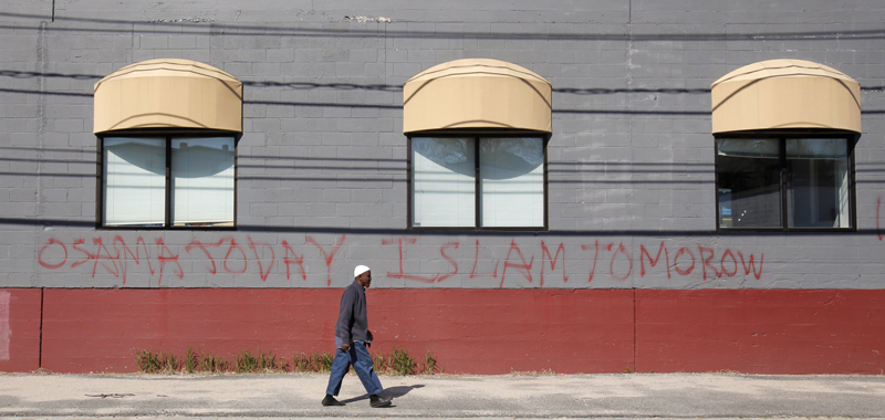 Jirde Mohamed walks past the front of a mosque on Anderson Street in Portland today where someone spraypainted graffiti on the wall in the wake of Osama Bin Laden's death. Bin Laden and Islam are not the same thing, said Mohammed, a member of the mosque who has lived in Portland 10 years.