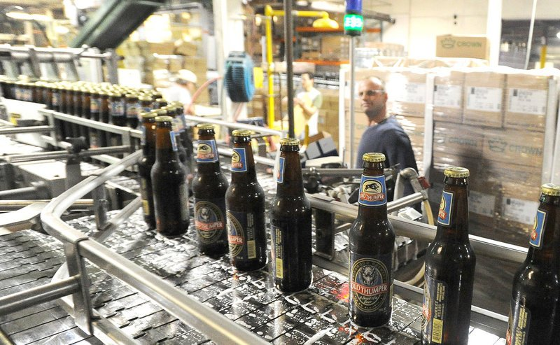 Just-filled bottles of Old Thumper file past an employee at Shipyard Brewing in Portland. About 15 types of beer are made under the Shipyard brand.