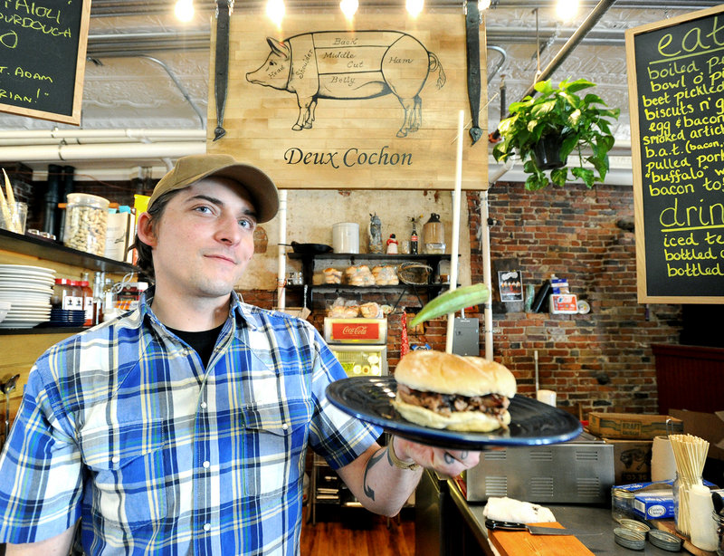 Adam Alfter, owner and chef, with a pulled pork sandwich at Deux Cochon in the Public Market House in Portland.