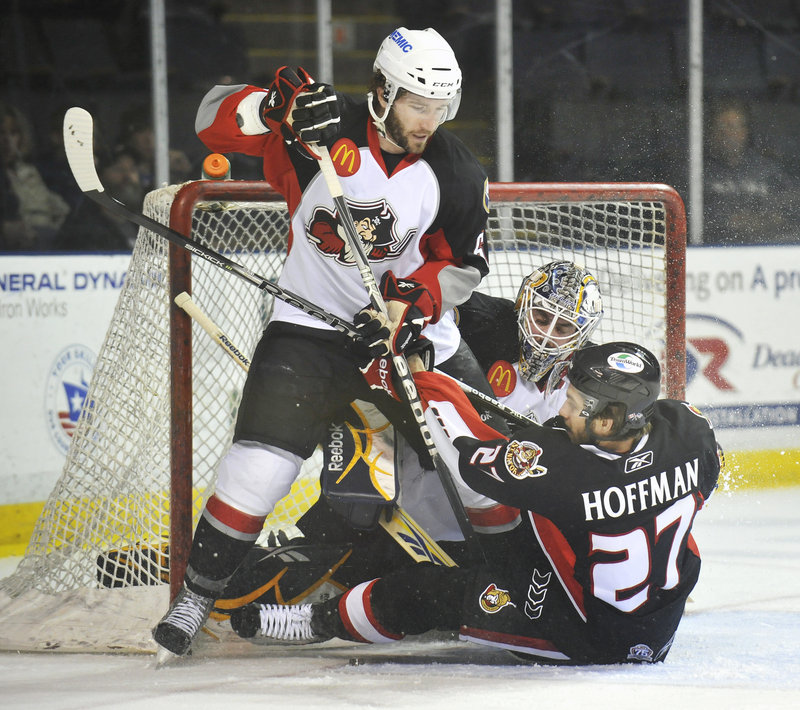 Binghamton s Mike Hoffman slides into Portland goalie Jhonas Enroth after being knocked to the ice by Portland s Brian O Haney on Friday night.