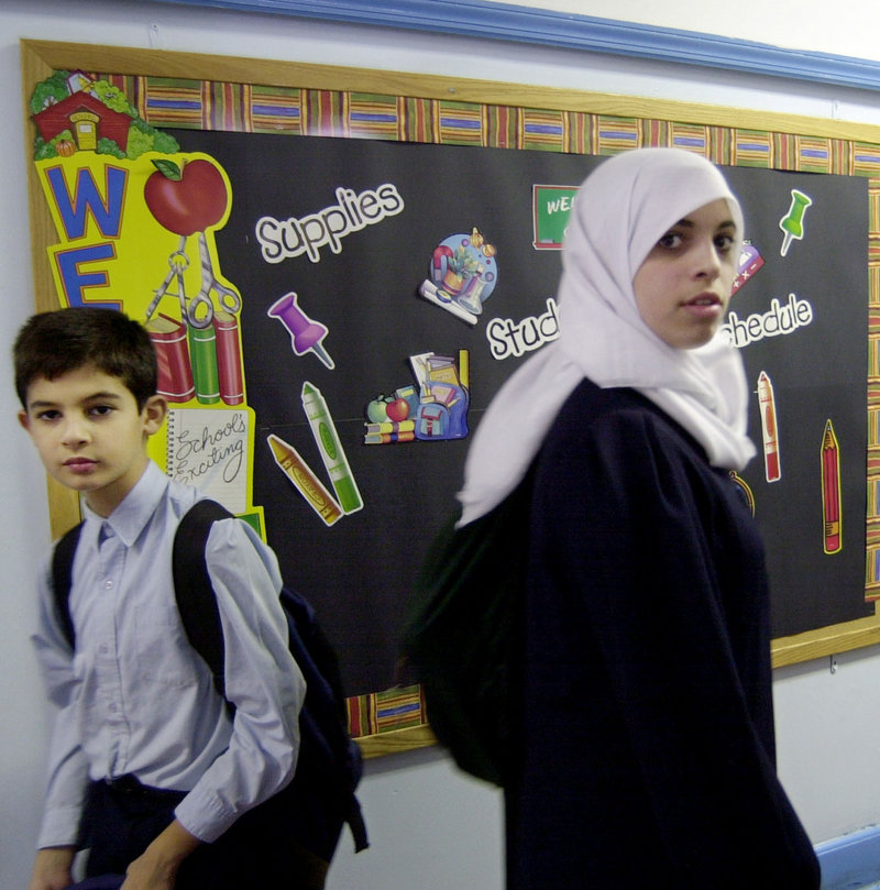 A Muslim girl passes a boy in a hallway at a school in Brooklyn, N.Y. Some young Muslims are hoping the death of Osama bin Laden will help end an era of suspicion against Muslims that began with 9/11.