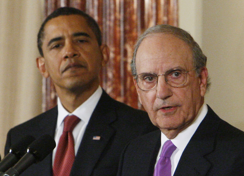 President Obama looks on as George Mitchell speaks at the State Department in 2009.