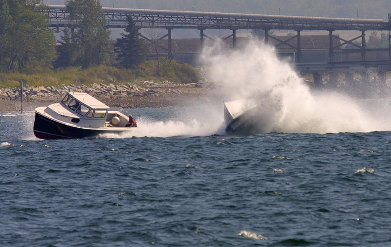 A lobster boat, right, rolls over as another one pulls ahead during a Maine Lobster Boat Race in Searsport.