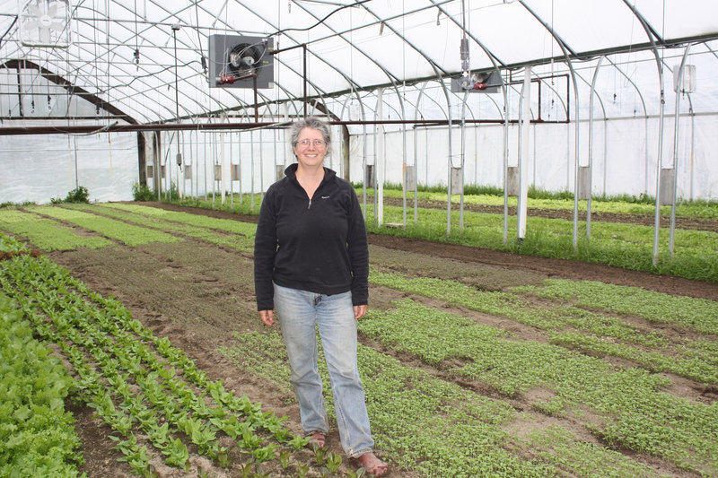 Farmer and cookbook author Lisa Turner stands inside one of the six greenhouses on Laughing Stock Farm in Freeport, which she runs with her husband, Ralph Turner. This greenhouse is planted with lettuce and greens that will be harvested in a couple of weeks.