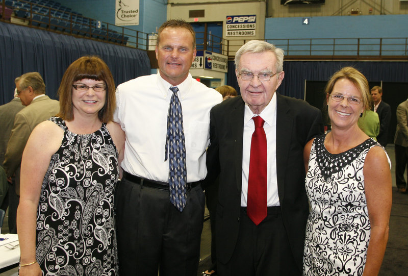 Dick McGee, honored for a long career as a football player, coach and athletic director, is joined by his daughters, Susan Perkins, left, and Marcia Goodhue, and his son, Mike, a longtime boys' basketball coach at Lawrence High.