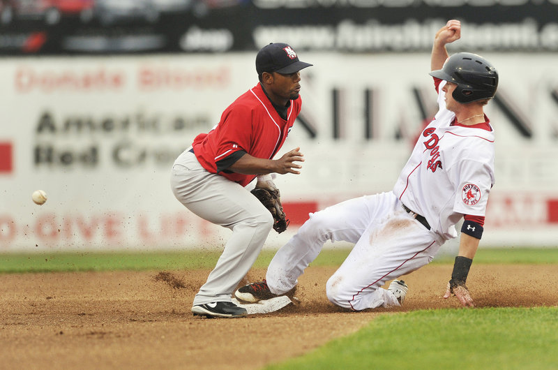 Jeremy Hazelbaker of the Portland Sea Dogs reaches second base with a steal as the ball skips past Callix Crabbe, the second baseman for the New Hampshire Fisher Cats.