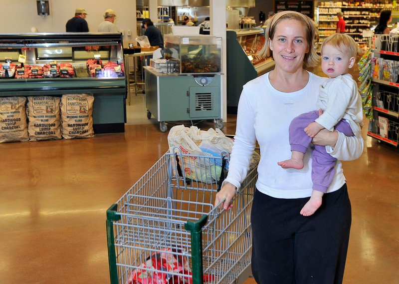 Caroline Loder, newly arrived from Germany and carrying daughter Savanah, 1, at the Bow Street Market in Freeport, says she is reeling from the cost of feeding her family of five an organic vegetarian diet. Her bill soared from $100 a week in Germany to $300 in Maine.