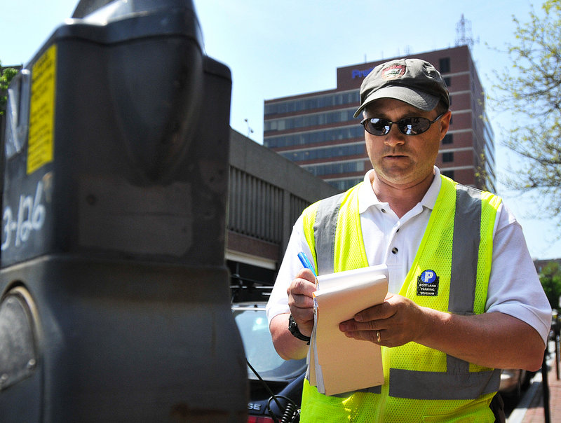 Parking Control Officer Chuck Fagone writes a ticket at a meter in Portland's Old Port.