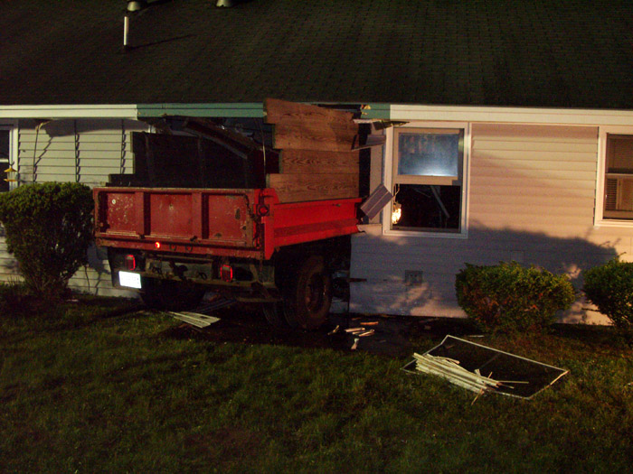 A Lovell man is charged with driving under the influence of drugs after he drove his 1994 Ford one-ton dump truck, while naked, over a series of lawns and into the front of 21 Woodland Hills. Photos courtesy of the South Berwick Police Department.